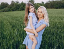 站在麦田里抱着女儿的妈妈摄影图片
