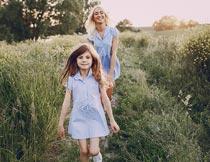 走在草丛间的蓝色裙子母女摄影图片