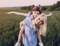 青色麦田间背着女儿的妈妈摄影图片