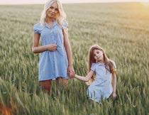黄昏牵手站在麦田里的母女摄影图片