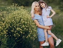 抱着站在黄色花丛旁的母女摄影图片