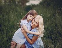 蹲在草丛间微笑相拥的母女摄影图片
