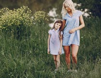 站花丛间穿蓝色裙子的母女摄影图片