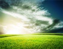 美丽黄昏下的云朵与草地风光摄影图片