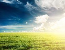 蓝天白云夕阳与草地美景摄影图片