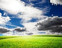 蓝天乌云与绿色草地美景摄影图片