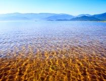 波光粼粼的金色湖水与山脉摄影图片
