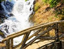 山林里的瀑布流水与木桥摄影图片