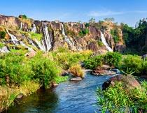 蓝天下美丽的岩石瀑布河流摄影图片