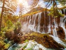 阳光下林间雄伟壮观的瀑布摄影图片