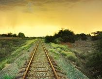 美丽黄昏草丛间延伸的铁轨摄影图片