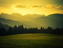 黄昏晚霞山峰绿树草地美景摄影图片