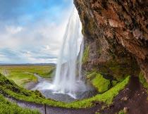 蓝天白云岩石瀑布草地风光摄影图片