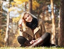 秋天树林里坐草地上的美女摄影图片