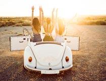 户外汽车上举手欢呼的美女摄影图片