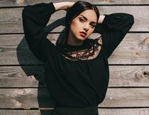 双手抱头靠木板的红唇美女摄影图片