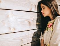 闭着眼睛靠木板的红唇美女摄影图片