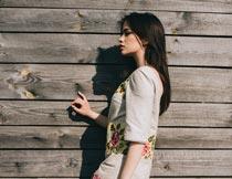 站在木板墙壁前的美女模特摄影图片