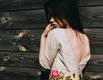 木板墙壁前露背的性感美女摄影图片