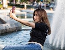 公园喷泉前手机自拍的美女摄影图片