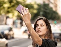 城市马路旁手机自拍的美女摄影图片