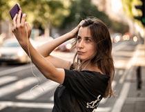 城市道路旁手机自拍的美女摄影图片