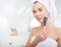 头戴浴巾粉底刷化妆的美女摄影图片