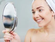 戴浴巾微笑着照镜子的美女摄影图片