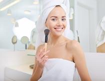 手拿粉底刷化妆的性感美女摄影图片