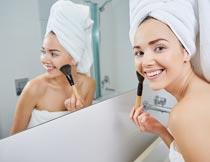 微笑照镜子化妆的性感美女摄影图片