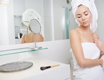 浴室梳妆台前戴浴巾的美女摄影图片