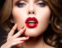 手摸脸颊张开红唇的美女摄影图片