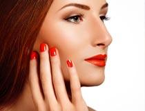 手摸脸颊的红唇美甲模特摄影图片