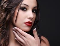 手摸下巴的红唇美甲美女摄影图片