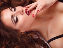 手摸红唇的性感卷发美女摄影图片