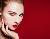 手托着下巴的红唇美甲模特摄影图片
