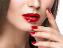 摸脸颊的性感红唇美甲模特摄影图片