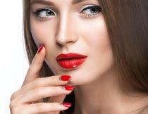 手摸脸颊的红唇美甲美女摄影图片