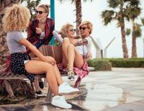 公园长椅上开心聊天的美女摄影图片