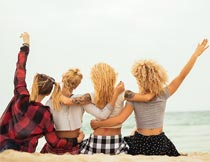 坐沙滩上欢呼的美女背影摄影图片