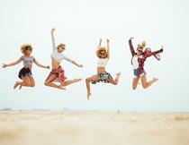 沙滩上跳跃欢呼的一群美女摄影图片