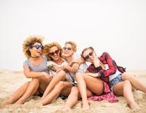 坐在沙滩上互相依靠的美女摄影图片