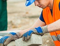 戴安全帽和手套砌砖的男人摄影图片