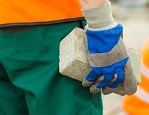 戴着手套双手拿砖块的男人摄影图片
