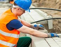 道路上戴手套砌砖的工人摄影图片