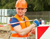 头戴安全帽拉隔离带的工人摄影图片