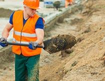 工地上挖土拉电缆线的工人摄影图片