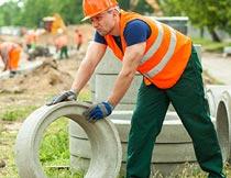 工地上搬运水泥管道的男人摄影图片
