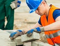 工地上铺设地面砖的男人摄影图片