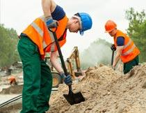 认真铁铲挖土施工的男人摄影图片